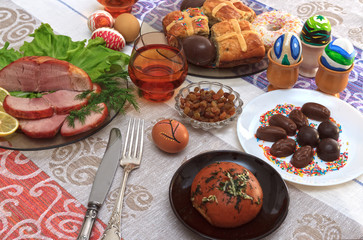Traditional easter dinner set with sliced meat with lemon and herbs, bread, handmade colored eggs, chocolates, raisins, easter cake and glasses of juice on colorful tablecloth