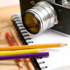 Closeup Composition with mechanic photocamera, pencils and a notebook