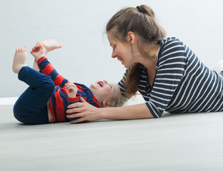 Mom plays with the baby lying on the floor