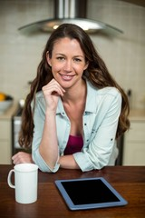 Young woman in kitchen with coffee mug and digital tablet on wor