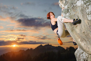 Young female rock climber climbing challenging route on overhanging cliff against scenic sunset background. Summer time.