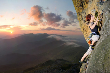 Athletic female rock climber climbing challenging route with rope and carbines on rocky wall against scenic sunset background. Summer time.