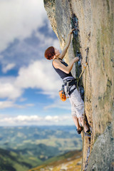 Young female rock climber climbing with rope and carbines an overhanging cliff against blue sky and mountains background. Summer time.