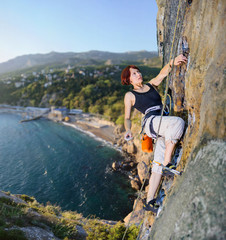 Woman climber conquers steep rock, searching for the next move to clamp the carbine, against the scenic sea coast on the background.