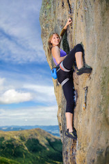 Blonde female climber on the steep overhanging rock cliff against blue sky and mountains. Smiling and looking at the camera. Summer time.