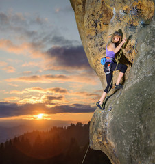 Rock climbing blond woman climbing challenging route with rope and carbines on rocky wall against scenic sunset background. Summer time. 1x1