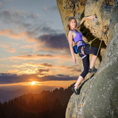 Young pretty female climber climbing with rope and carbines on large boulder against scenic sunset background. Hanging on one hand, smiling and looking at the camera. Summer time. 1x1