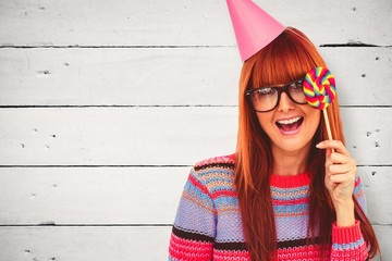 Composite image of smiling hipster woman with lollipop and hat
