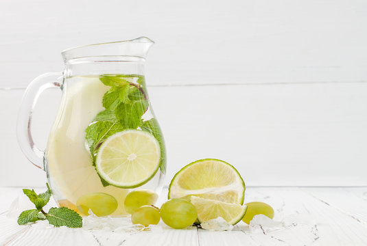 Refreshing homemade lime and mint cocktail over old vintage wooden table. Detox fruit infused flavored water. Clean eating. Copy space background