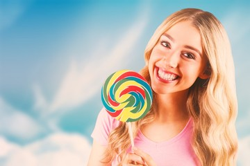 Composite image of a beautiful woman holding a giant lollipop