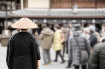 神社の参道に佇む托鉢僧