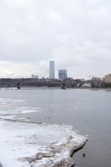 Вид Москвы-реки и зданий на берегу зимним пасмурным днём. Москва. Россия.