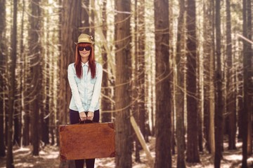 Portrait of a hipster woman holding suitcase
