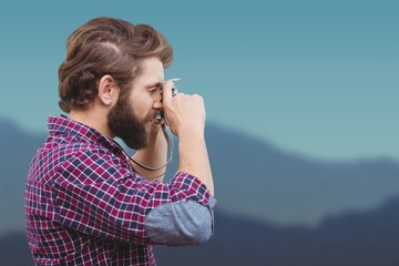 Composite image of side view of hipster photographing with camera
