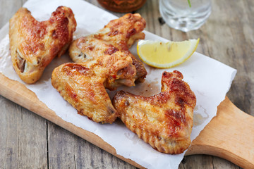 Grilled chicken wings with lemon on wooden chopping board.horizontal