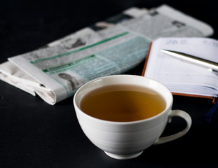 Cup of tea on the table with newspaper and notebook