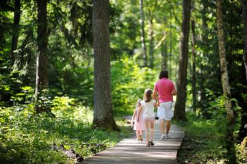 Happy family of three taking a walk in a sunny park