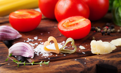 Italian food background with vine tomatoes, basil, spaghetti, olives Ingredients on stone table