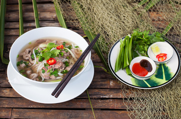Traditional Vietnamese beef soup pho with sous Hoisin on a wooden background