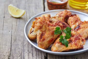Hot meat dishes -Baked chicken wings with parsley and lemon on plate