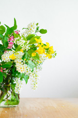 Bouquet of wild spring flowers - rapeseed and european bird cherry - in a jar. Selective focus