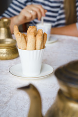 Shortbread biscuits in white cup and woman stirring tea in a cup in the background. Biscuits are the food specialty of Lanquedoc region of France, called zezette. Selective focus.