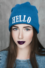Fashion hipster woman with backpack in blue hat and gray dress