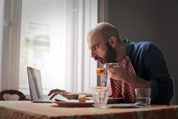 Man eating while surfing the Net