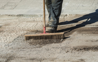 worker with large scrub brush collect residues of asphalt milling