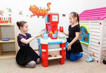 Two little girls play role game with toy kitchen in day care