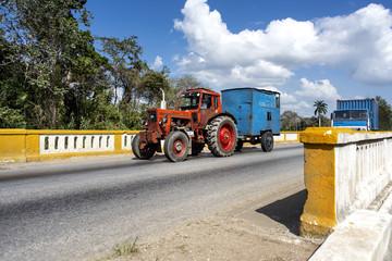 Kuba: Alter roter Traktor fährt mit Anhänger über eine traditionell gebaute kubanische Brücke - Transport