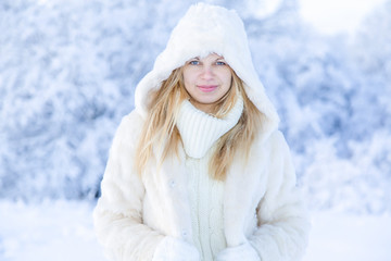 Portrait of nice beautiful young woman in white sweater and fur coat