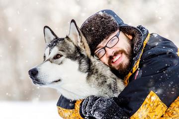 a man with a beard and dog malamute