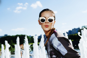 Portrait of beautiful young girl in sunglasses in the city