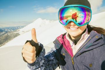 Happy girl dressed in ski or snowboard fashion mask goggles