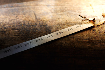 Global warming, Climate change, rising temperature through the decades. Paper strip with timeline charred and burnt on the far end, placed on old wooden table.