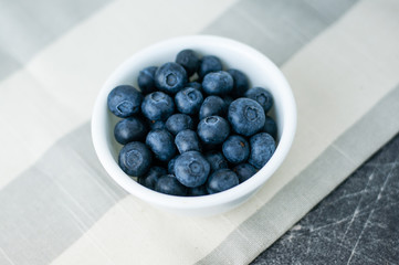 Small white bowl of blueberries linen tablecloth close up top view