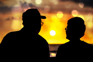 夕日を見つめるシニアのカップル