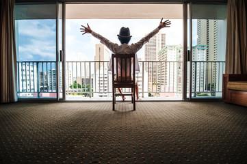 椅子に座って窓から景色を眺める男性