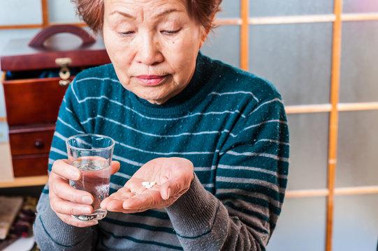 薬を手に持っている高齢者の女性