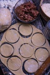 Raw meat dumplings. Ingredients for making dumplings: dough, minced meat, eggs on the wooden background