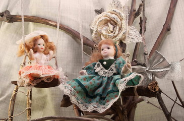 Porcelain dolls on swings photo. Two pretty porcelain dolls on swings photo.