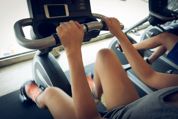 woman exercise riding bicycle in fitness center, activity of hea