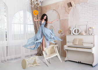 funny girl clowns jumping on chairs and holding a fan,fashionable toning,creative computer colors