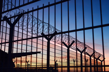 Barbed wire fence around a French immigration border with a beautiful colorful sky in the background located in Dieppe France
