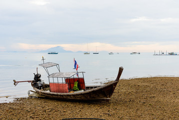 Longtail boat park on sand at krabi
