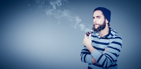 Composite image of portrait of serious hipster smoking pipe