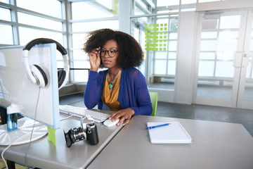 Portrait of a smiling woman with an afro at the computer in bright glass office