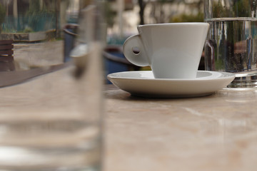 Espresso cup between two glasses on a marble table in a cafe