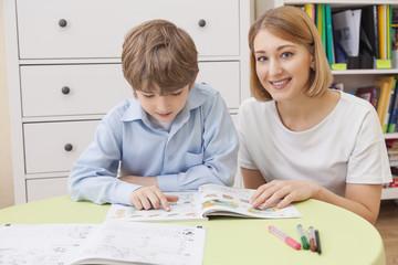 caucasian boy reading a textbook. Beside him sits a teacher